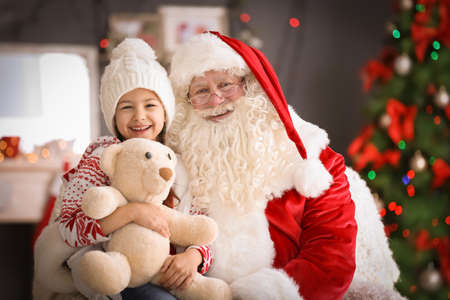 Little girl with teddy bear sitting on authentic Santa Claus' lap indoors Stock Photo