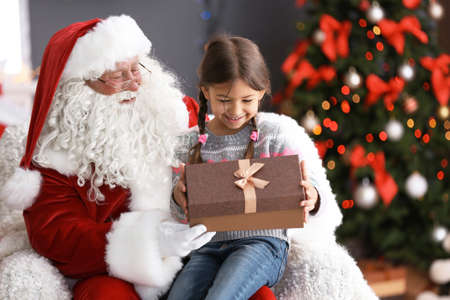 Little girl with gift box sitting on authentic Santa Claus lap indoors