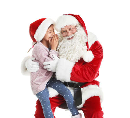 Little girl whispering in authentic Santa Claus ear against white background Stock Photo