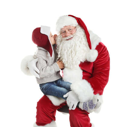 Little boy whispering in authentic Santa Claus' ear against white background