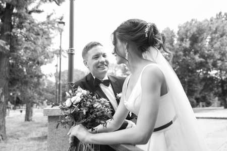 Happy newlyweds with beautiful bridal bouquet outdoors, black and white effect