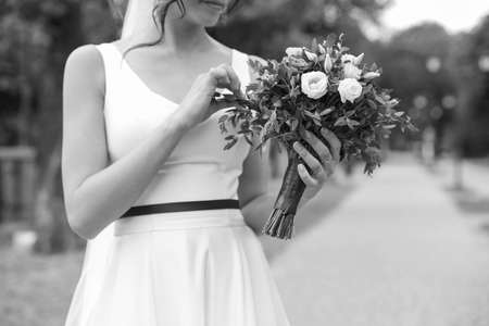 Woman in wedding gown with beautiful bridal bouquet outdoors, black and white effect