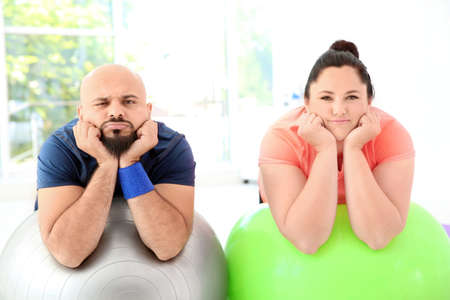 Tired overweight man and woman resting on fitness balls in gym Archivio Fotografico - 106360877