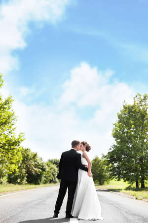 Bride and her groom kissing on highway Stock Photo