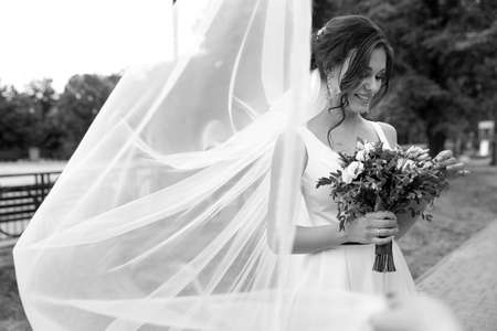 Young bride with bouquet in long veil outdoors, black and white effect Stock Photo