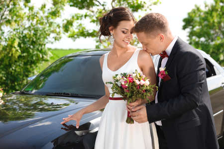 Happy bride and groom near car outdoors