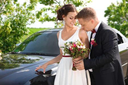 Sposa e sposo felici vicino all'automobile all'aperto
