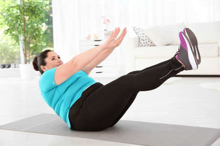 Overweight woman doing exercise on mat at home