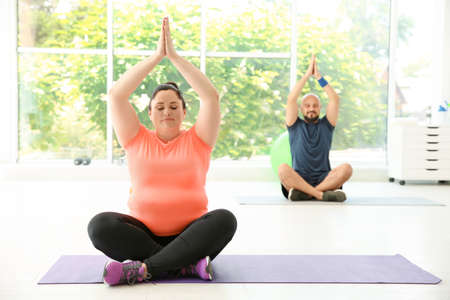 Overweight man and woman practicing yoga in gym Stock Photo