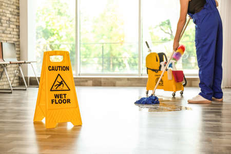 Safety sign with phrase Caution wet floor and cleaner indoors. Cleaning service