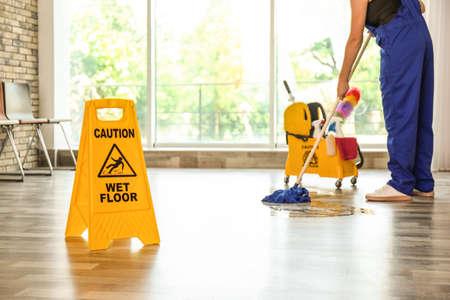 Segnale di sicurezza con frase attenzione pavimento bagnato e detergente al chiuso. Servizio di pulizia