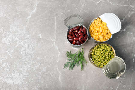 Flat lay composition with canned vegetables on grey background