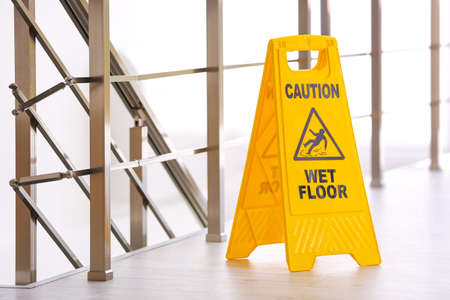 Safety sign with phrase Caution wet floor, indoors. Cleaning service 写真素材