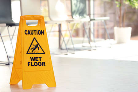 Safety sign with phrase Caution wet floor, indoors. Cleaning service 스톡 콘텐츠