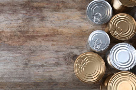 Many tin cans on wooden background, top view. Recycling garbage Stock Photo