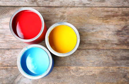 Tin cans with paint on wooden background, top view