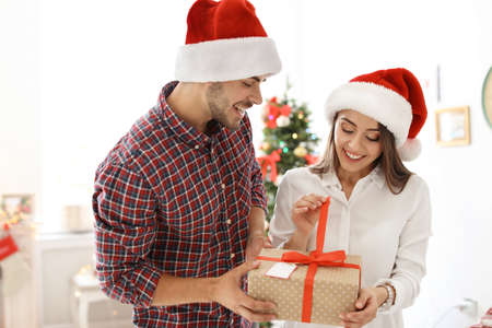 Young couple with Christmas gift at home