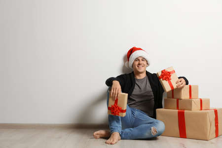 stock photo young man with christmas gifts near white wall