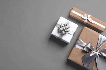 Beautifully wrapped gift boxes on grey background, top view