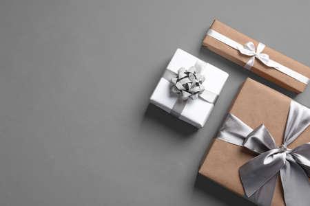 Prachtig ingepakte geschenkdozen op grijze achtergrond, bovenaanzicht
