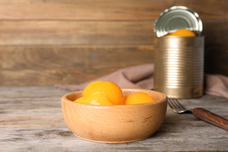 Bowl with canned peaches on wooden table Banco de Imagens