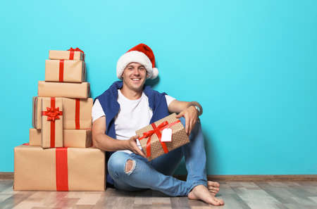 stock photo young man with christmas gifts near color wall