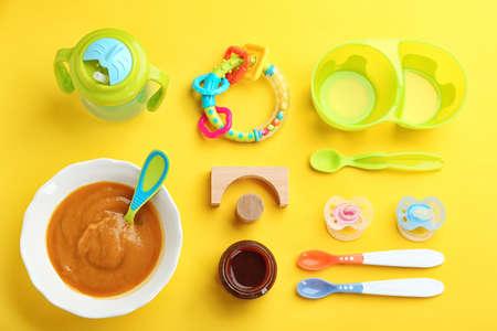 Flache Laienkomposition mit Babynahrung und Zubehör auf farbigem Hintergrund Standard-Bild