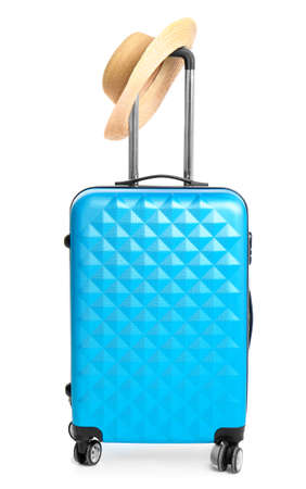 Blue suitcase with hat on white background