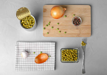 Flat lay composition with canned green peas on grey background Banco de Imagens