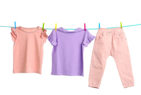 Child clothes on laundry line against white background