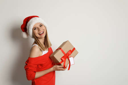 Young woman with Christmas gift on white background Stock Photo