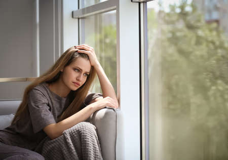 Depressed young woman sitting on sofa at home Banco de Imagens