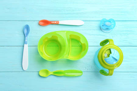 Flat lay composition with baby tableware for food on wooden background