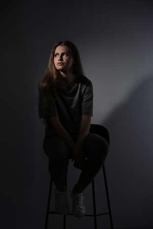Deprimierte junge Frau auf grauem Hintergrund