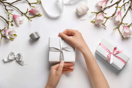 Woman with beautiful gift boxes on white background, top view Фото со стока