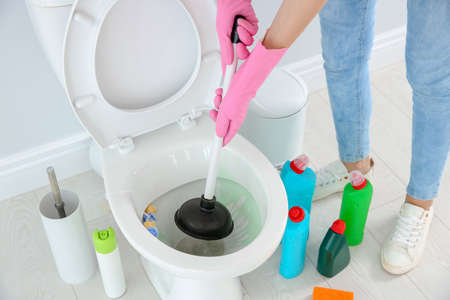 Woman cleaning toilet bowl in bathroom