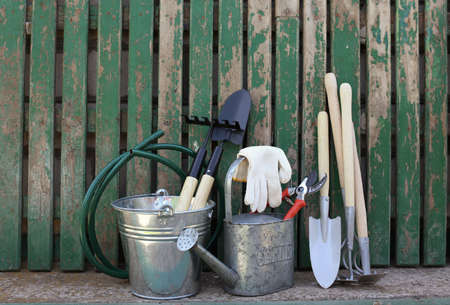 Set of gardening tools near wooden fence