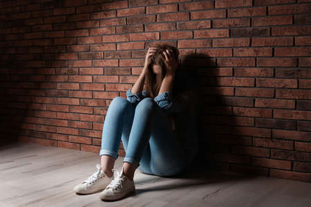 Depressed young woman sitting on floor near brick wall Stock Photo