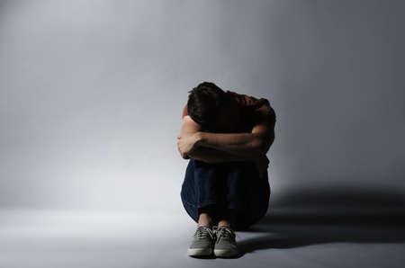 Homme déprimé solitaire assis sur fond gris Banque d'images