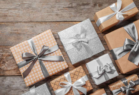 Beautiful composition with Christmas gift boxes on wooden background, top view