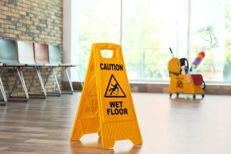 Señal de seguridad con la frase Precaución piso mojado, en interiores Foto de archivo
