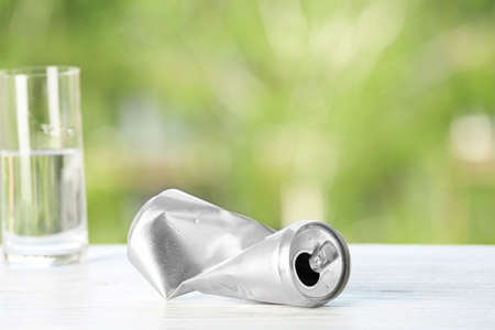 Crumpled aluminum can on table against blurred background. Metal waste recycling
