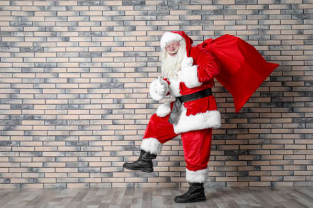 Authentic Santa Claus with big red bag full of gifts near brick wall Foto de archivo