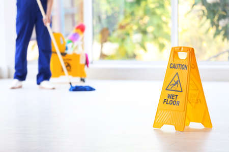 Safety sign with phrase Caution wet floor and blurred cleaner on background Banque d'images