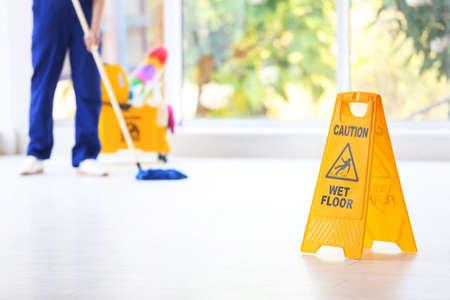 Sicherheitszeichen mit Satz Vorsicht nasser Boden und unscharfer Reiniger auf Hintergrund