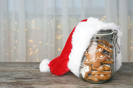 Glass jar with tasty homemade Christmas cookies and Santa hat on table