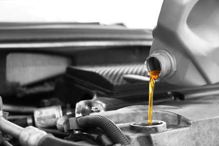 Giet olie in de motor van een auto, close-up