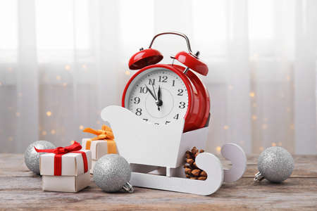 Retro alarm clock, gifts and festive decor on table. Christmas countdown