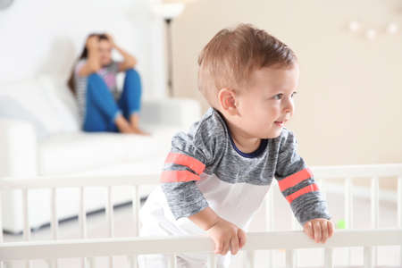 Cute baby boy in crib and young mother suffering from postnatal depression on blurred background