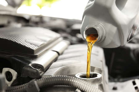 Pouring oil into car engine, closeup Reklamní fotografie